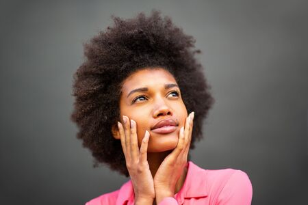 Close up portrait of beauty young african american woman with hands on face against gray wall