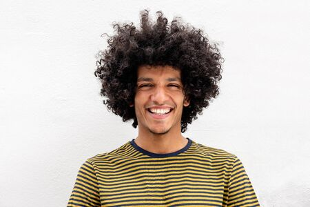 Close up front portrait of handsome young North African man smiling by white background