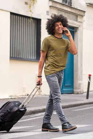Full body portrait of happy young man with afro walking and talking on street with mobile phone and luggage
