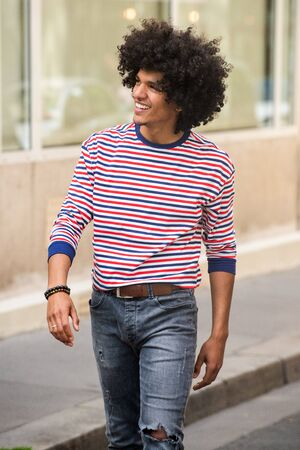 Portrait of cool young arab guy with afro hair walking on street outside and looking away Stock Photo