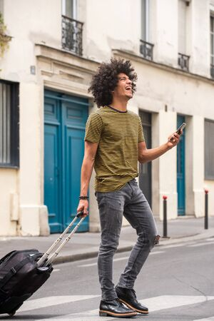 Full body portrait of happy young man with afro walking on street with mobile phone and luggage