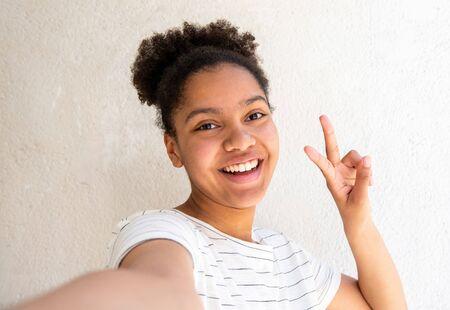 Chiuda sul ritratto di giovane ragazza afroamericana felice che prende selfie contro il fondo bianco con il segno della mano di pace Archivio Fotografico