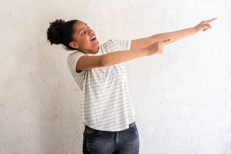 Portrait of young african american girl pointing fingers to side by white background