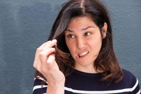 Close Up retrato de mujer joven sosteniendo su cabello con expresión infeliz Foto de archivo