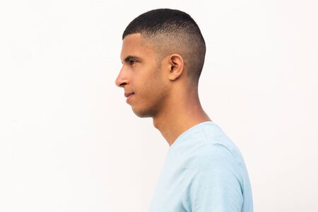Profile portrait of young North African man with serious expression by isolated white background Stock Photo