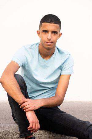 Portrait de jeune homme arabe assis sur le sol avec une expression sérieuse
