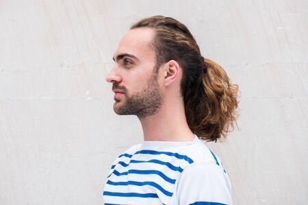 Nahaufnahme Seitenporträt eines jungen Mannes mit langen Haaren im Pferdeschwanz von weißem Hintergrund Standard-Bild