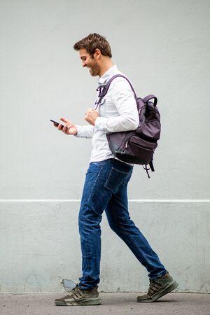 Retrato de cuerpo entero del hombre de viaje feliz con bolsa mirando el teléfono móvil por la pared gris