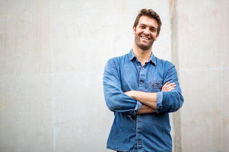 Portrait mec plus âgé souriant avec les bras croisés par un mur blanc Banque d'images