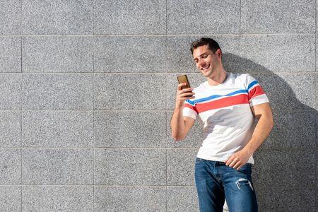 灰色の壁で携帯電話を見ながら微笑む若者の肖像画 写真素材