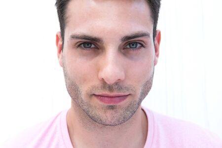 Nahaufnahme des vorderen Porträts eines gutaussehenden jungen Mannes, der durch weißen Hintergrund starrt Standard-Bild