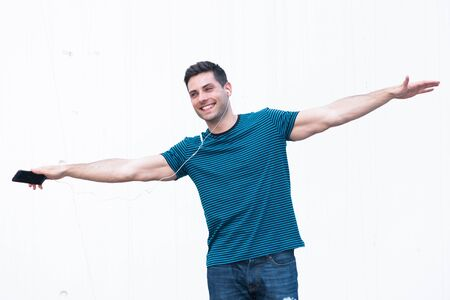 Portrait of happy young man with mobile phone and ears spreading arms out like airplane