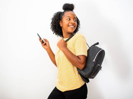 Side portrait african american teenager girl with cellphone and bag turning around isolated white background