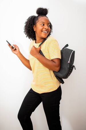Profile portrait of smiling african american girl with bag and mobile phone turning isolated white background Stock Photo