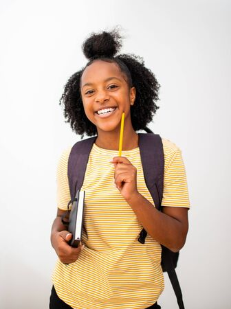 Portrait happy smiling african american girl student with bag and books standing by isolated white background