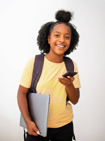 Portrait african american teenage girl smiling with mobile phone laptop and bag isolated white background Zdjęcie Seryjne