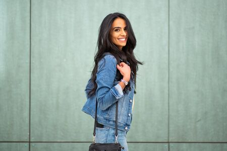 Side portrait smiling young latin woman with handbag by green wall