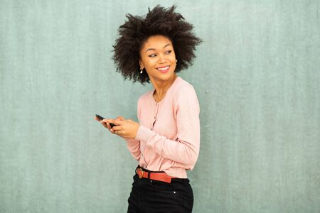 Portrait smiling young african american woman holding phone by green background and turning around Archivio Fotografico