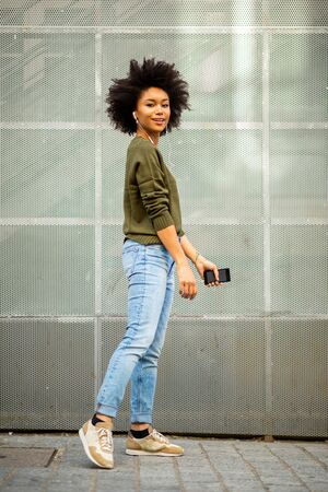 Full length side portrait beautiful young african woman with mobile phone and earphones