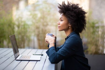 Side portrait young african american business woman sitting with laptop and cup of coffee
