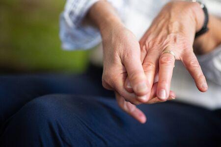 Close up portrait older woman hands touching fingers