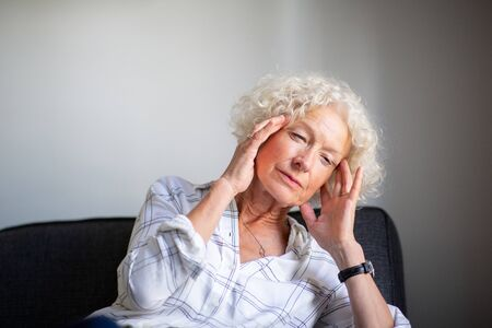 Portrait older woman sitting on sofa with headache and hands to head