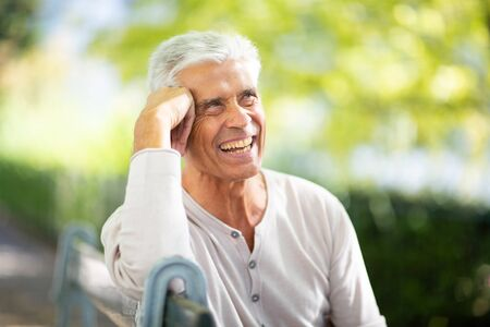 Close up portrait handsome older man sitting on park bench and smiling
