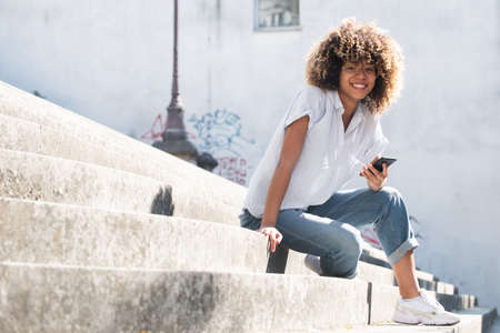 Portrait smiling young African American woman with eyeglasses sitting outside holding mobile phone