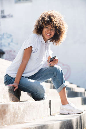 Portrait smiling young black woman with eyeglasses sitting outside holding mobile phone Stockfoto