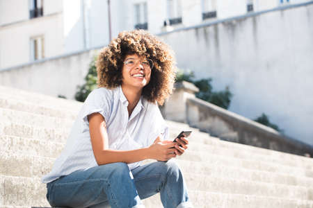 Portrait attractive young black woman smiling with mobile phone outside