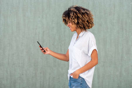 Side portrait smiling young African American woman looking at cellphone by green wall
