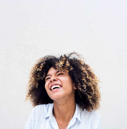 Close up portrait young african american woman laughing against white background Stockfoto