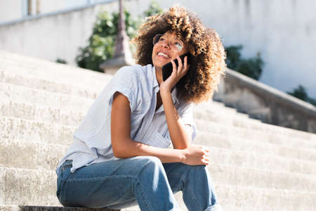Portrait happy young black woman with eyeglasses sitting outside talking on cellphone