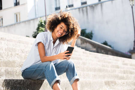 Portrait smiling young woman with eyeglasses sitting outside looking at phone