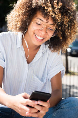 Close up portrait happy young African American woman listening to music with mobile phone and earphones