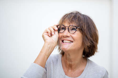Close up portrait older woman smiling with eyeglasses by white background and looking away