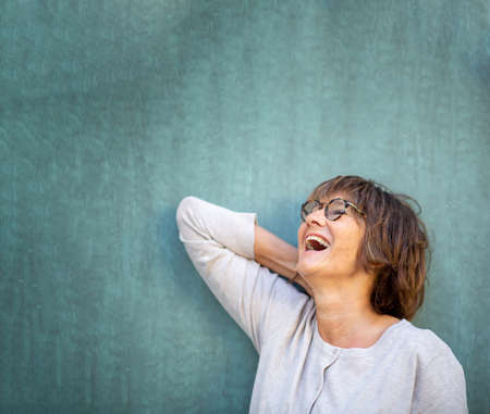 Close up portrait older woman laughing with eyeglasses against green wall