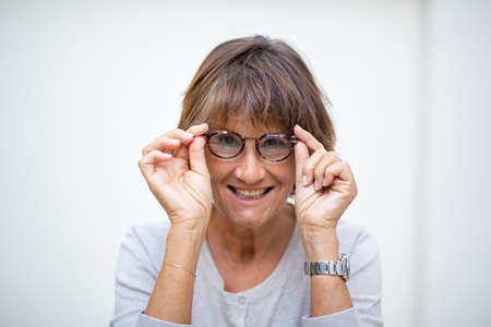 Close up portrait older woman smiling with eyeglasses by white background
