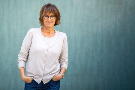 Portrait older woman with serious expression and eyeglasses by green background Stockfoto