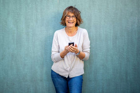 Portrait woman smiling with mobile phone by green wall