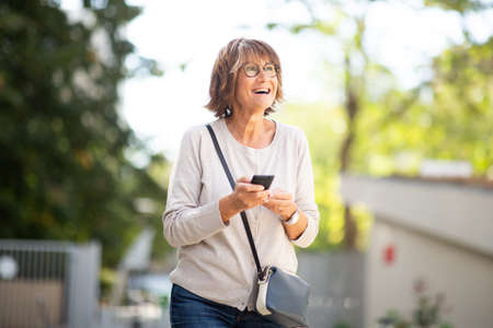 Portrait happy older woman laughing with mobile phone outside