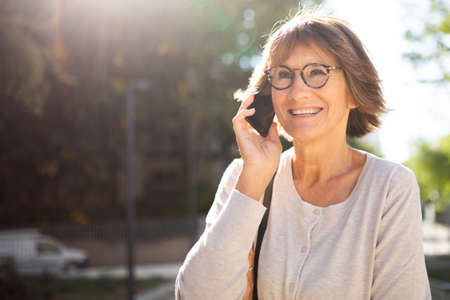 Close up portrait happy woman with glasses talking on cellphone