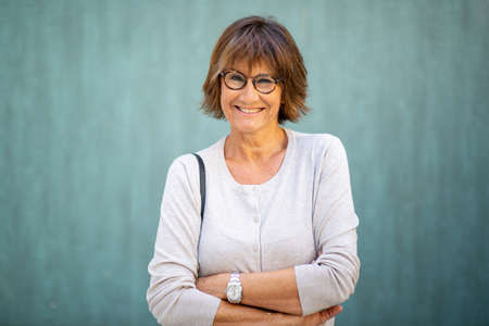Portrait elderly woman smiling with eyeglasses and arms crossed Stockfoto