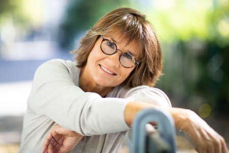 Close up portrait happy older woman with glasses relaxing on park bench Stockfoto