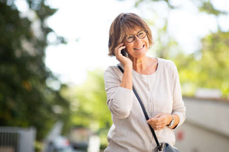 Portrait older woman talking with cellphone outdoors