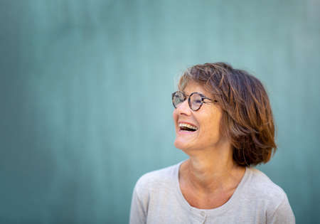 Close up side portrait woman in 50s laughing by green background Stockfoto