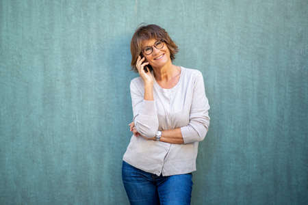 Portrait older woman talking with cellphone by green background Stockfoto