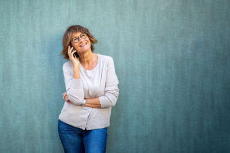 Portrait older woman talking with mobile phone by green background