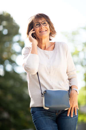 Portrait happy older woman talking with mobile phone outdoors Stockfoto
