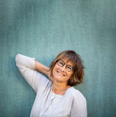 Close up portrait happy woman with glasses leaning against wall Stockfoto